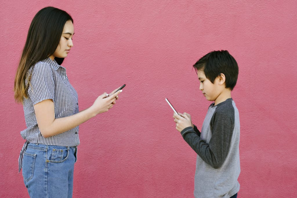 Mother with long brown hair and checkered collared shirt and jeans next to her adolescent boy with ADHD with short brown hair wearing a light gray shirt with dark gray long sleeves facing each other in front of a dark pill wall, both staring at their phones.
