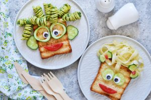 Creative looking meals with pasta hair and bread faces with vegatable facial features made by kids with ADHD for family dinnertime