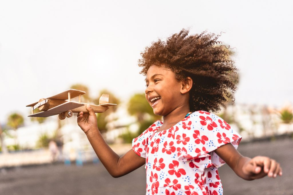 Young happy child with ADHD running on the beach while playing with wood toy airplane at sunset, overcoming the negative memory bias by spending time enjoying and celebrating her accomplishment of making the toy