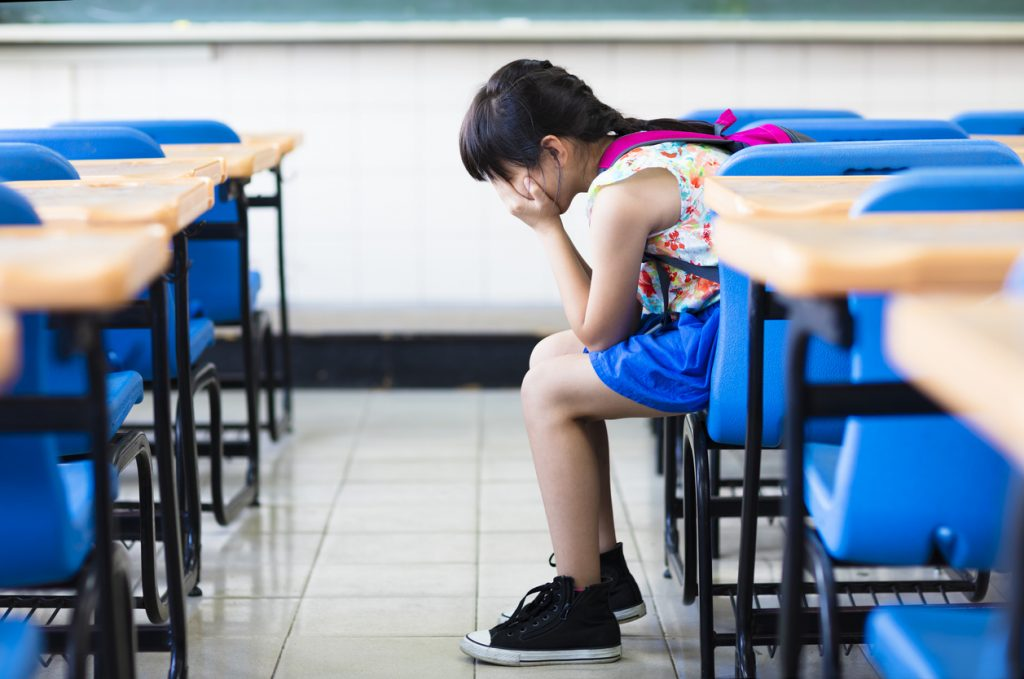 Young sad girl with ADHD wearing a flower shirt and pink backpack sitting alone in a classroom at a desk with blue chair turned to the side with her hands over her eyes, dwelling on a negative experience and showing the impact of the negative memory bias on kids