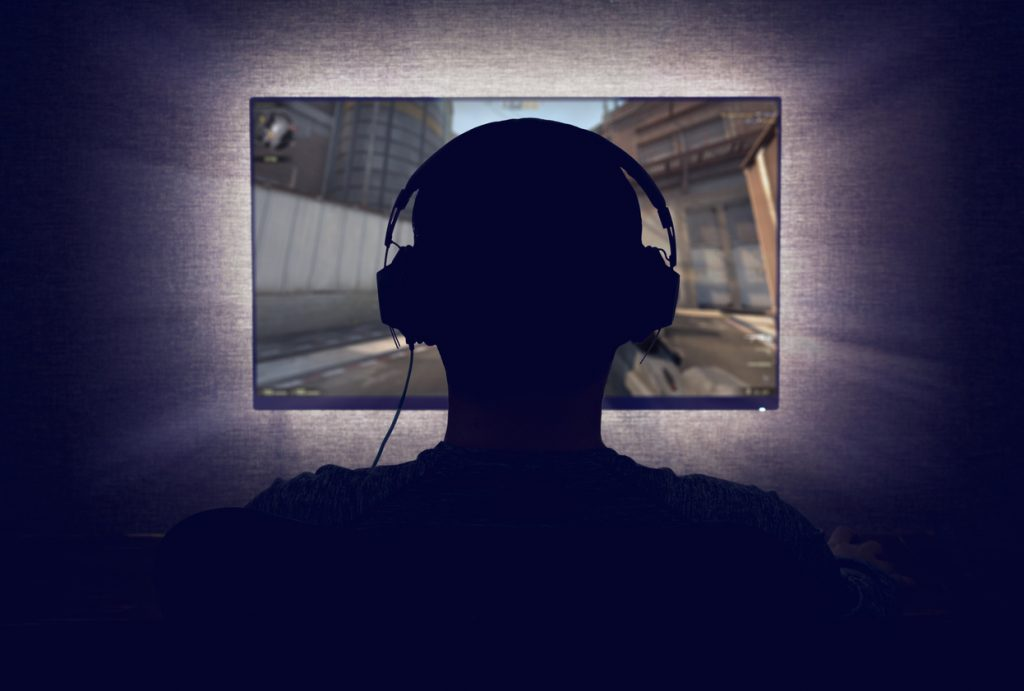 Sillhoette of teen with ADHD with over-ear headphones on while playing video games on a screen that is radiating light against a dark background