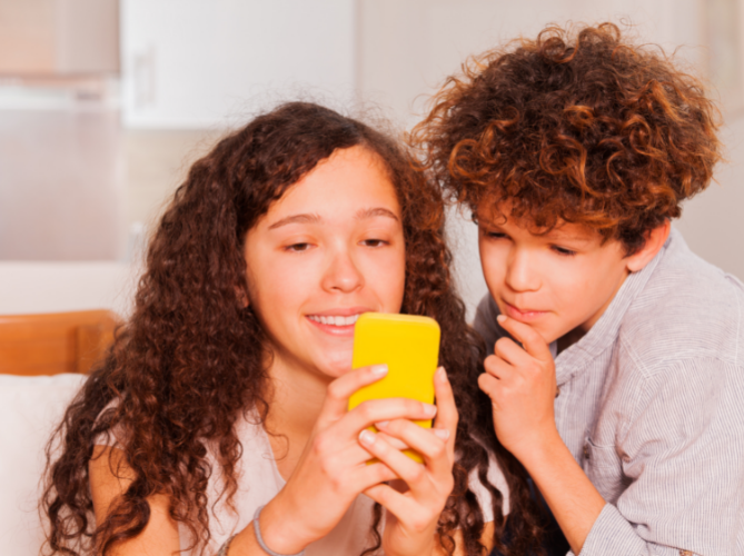 Older adolescent with ADHD and her younger brother, both with brown curly hair and cream colored tops, both look at a phone with a yellow case with great interest.