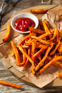 sweet potato fries on a wooden serving board with ketchup