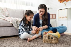 Child with ADHD learning to knit with mom next to her on the living room rug.
