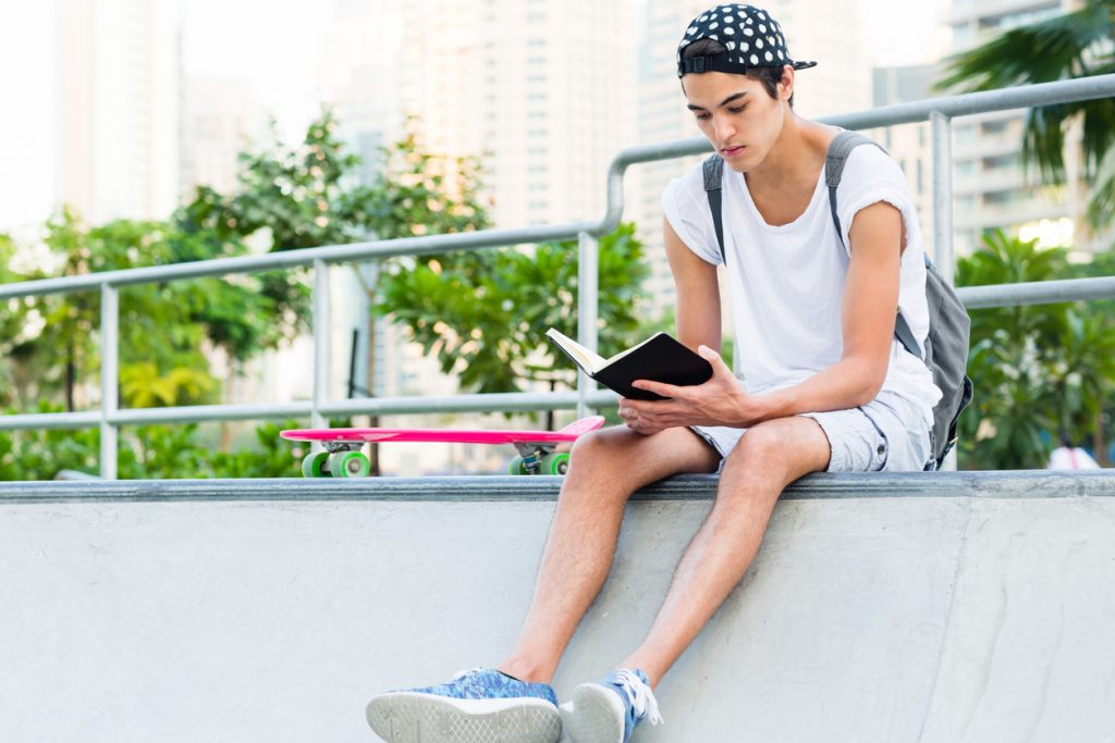 Teen sitting in a skatepark next to his skateboard reading his personal project journal