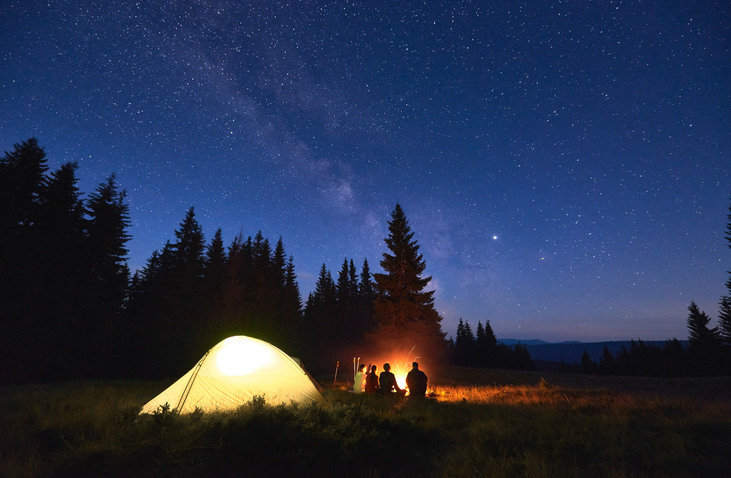 Family of 4 sitting outside in front of a fire while camping, they're next to a glowing yellow tent by pine trees under a starry night sky.