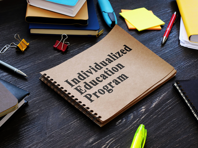 """Notebook with a cover titled """"Individualized Education Program"""" on a desk with other school supplies."""