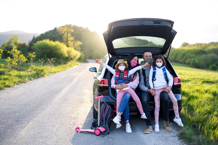 Neurodiverse family of 4 on a family outing sitting in the trunk of a hatchback, outside on a road during a sunset, wearing masks and backpacks, looking happy together.