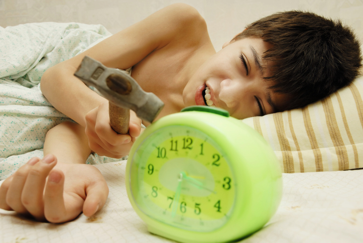 Child laying in bed holding a hammer and holding it to a green alarm clock.
