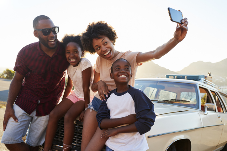 Neurodiverse family of 4 smiling and taking a selfie on the hood of a car on a sunny day in front of mountains on a family outing.