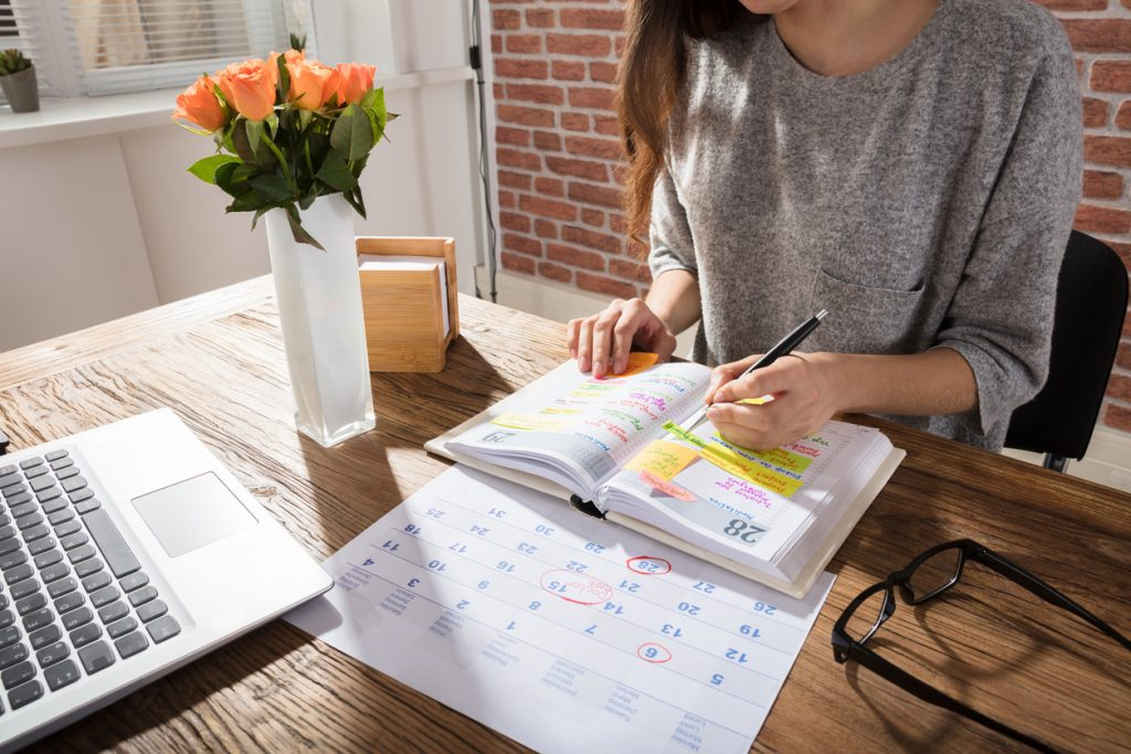 Woman with ADHD using a personal project planner on her living room table next to a computer, a pair of glasses, a calendar and a vase of orange tulips.