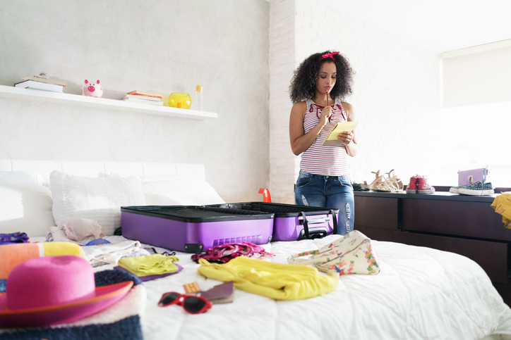 Neurodivergent girl with ADHD looking at a list to pack for a trip next to an empty suitcase on a bed with clothes laid on it.