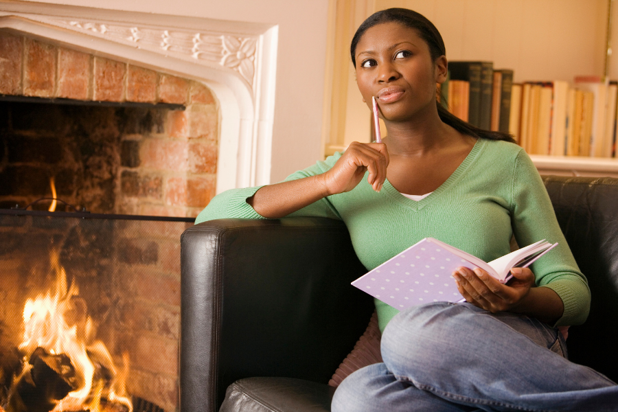 Person with ADHD sitting by a fireplace and holding a pencil to their face as they sit on a couch holding their personal project planner.
