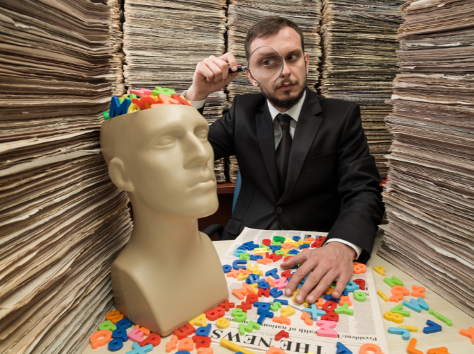 Man in a suit surrounded by newspapers holding a magnifying glass up to a plastic head filled with colorful plastic letters that are spilling over the table, looking like he is researching the brain
