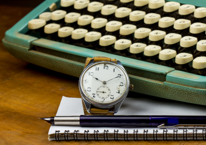 Picture of a watch, notebook and pen next to a classic green typewriter