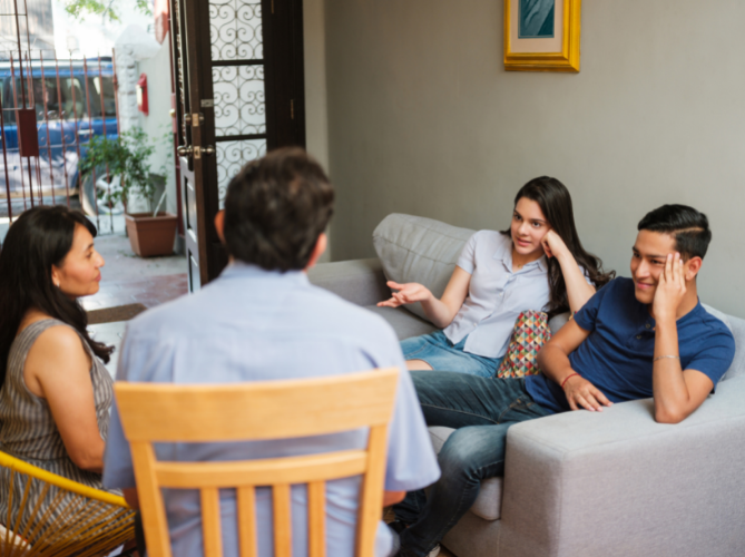 Neurodiverse family of four having a positive family meeting in the living room