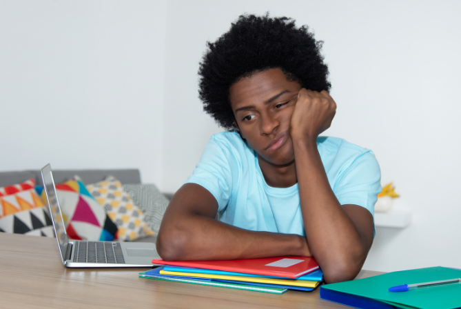 Teen boy with ADHD looking unmotivated and bored sitting at his desk with his arms over his folders next to his laptop