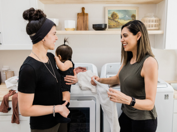 Couple with ADHD smiling and having a good time helping each other stay on task as one holds the baby and one folds laundry in their laundry. room.