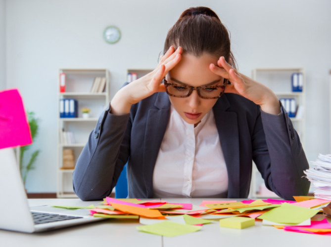 Stressed out professional adult with ADHD looking down at a desk of colorful sticky notes in front of her laptop while holding her head in her hands