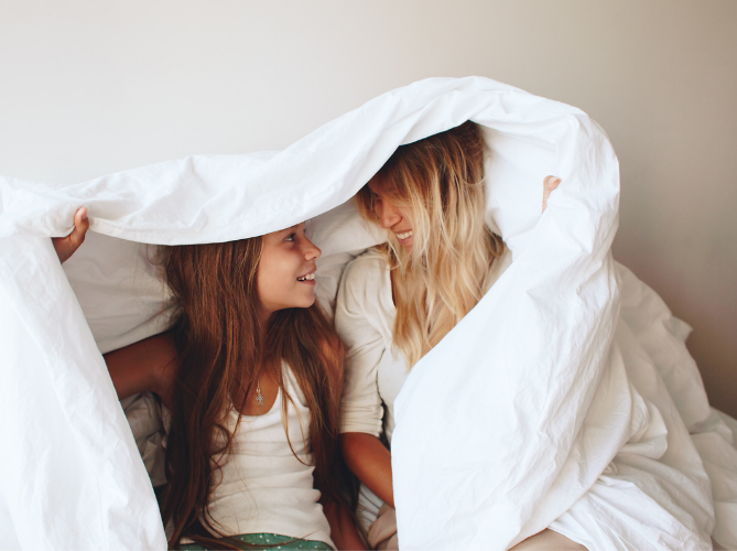 Mom and daughter with ADHD laughing together as they hide and talk under a blanket