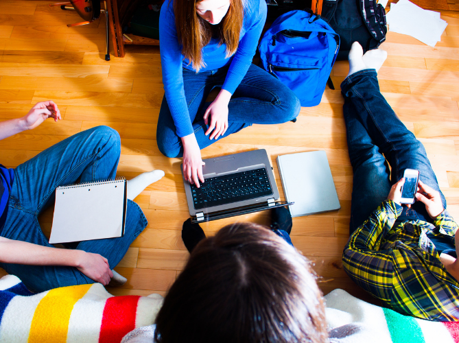 Group of neurodiverse teens in a circle working on homework together