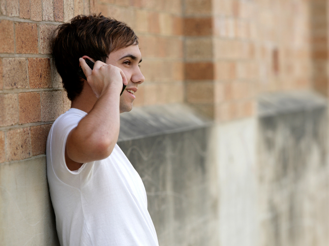 Teen boy leaning against a brick wall talking on the phone to a parent