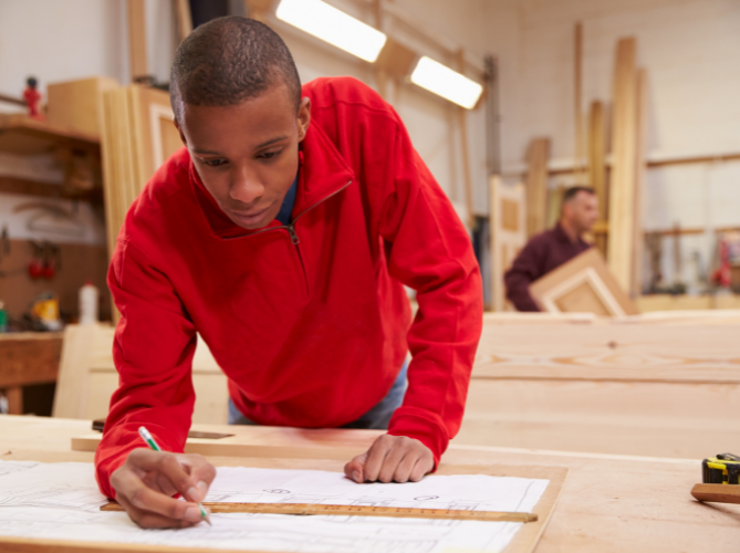 Teen with ADHD planning and drawing out a blueprint in a woodworking shop at school