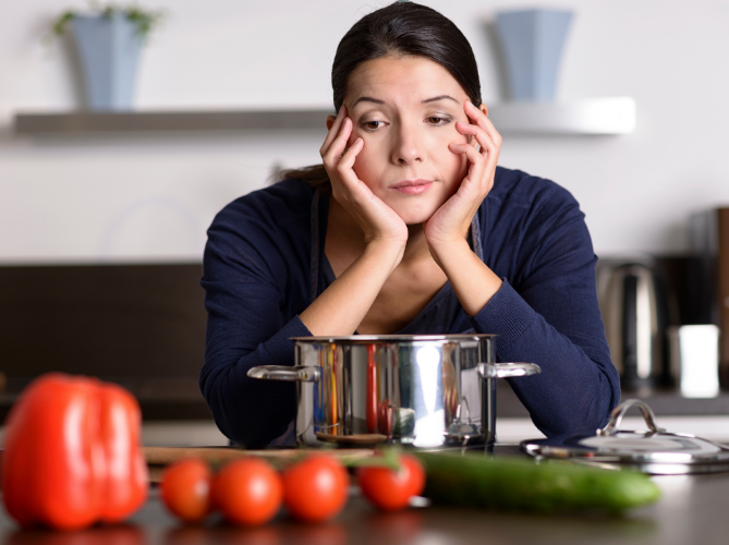 Woman with low motivation and ADHD, looking disinterested at the vegetables in front of her on the counter.