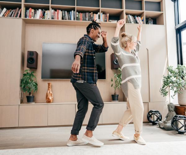 Two girls joyfully dancing in a large, sunlit living room