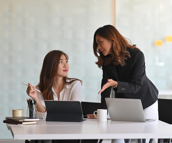 Person with ADHD sitting at her computer at an office while her boss standing beside her looks upset with her