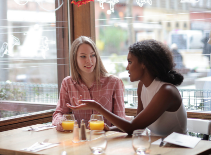 conversation between two women at a restaurant, one looking a bit unsure of what the other is saying
