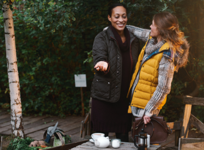 Couple with ADHD outside in the fall, standing, hugging and laughing in front of a table set with tea