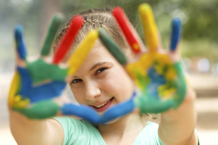 Image of girl with ADHD smiling as she looks through her colorful paint-covered hands she's holding up towards the camera