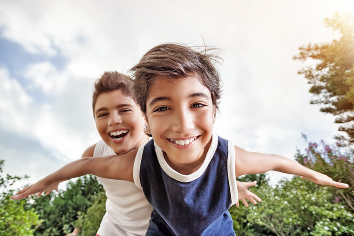 Point of view of someone playing basketball, playing against two neurodiverse kids smiling and having fun, while looking at one playing defense
